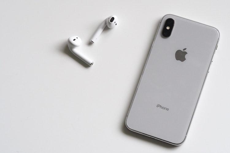 De huidige generatie AirPods naast een iPhone X