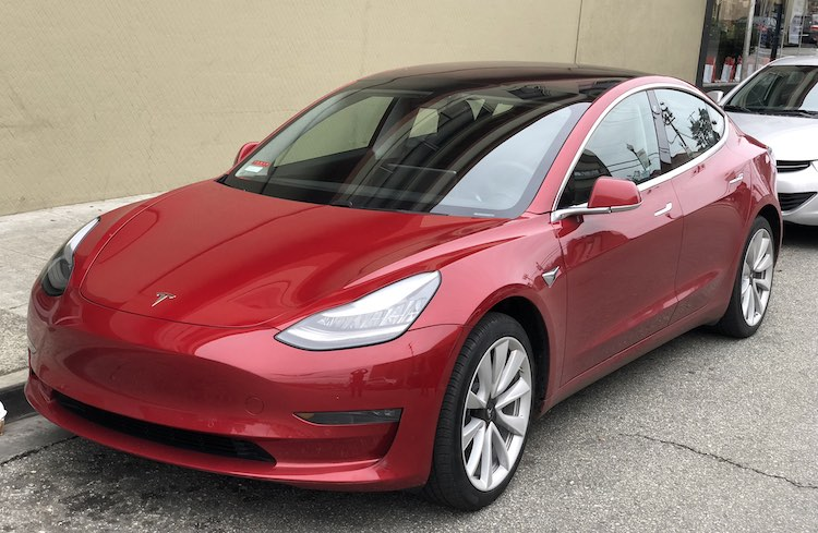 Man laat sleutel Tesla Model 3 in zijn hand aanbrengen